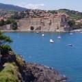 Imagen de Collioure, pueblo de sur de Francia. Se ve el mar, el castillo al borde del mar, y casas en la montaña, y la montaña.