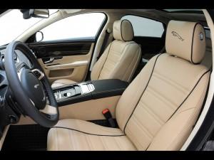 Interior del Jaguar XJ de 2011. Se ven los asientos en cuero beige, y el salpicadero en piel negra.