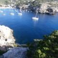 Imagen de Cala-Vadella-Ibiza, se ve el mar, barcos de vela, las rocas y la cala.