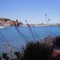 Vista del puerto de Collioure desde el restaurante de un hotel. Se ve parte de una mesa, el mar, y al fondo el castillo y el pueblo.