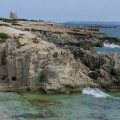 imagen de la costa-de-las-Salinas de-Ibiza. Se ve una torre vigía, las rocas de la costa, el mar y el cielo azul.