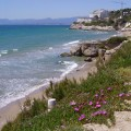 La Playa Larga de Salou, viéndose la costa, y al fondo edificios, y más allá las montañas, y a la izquierda el mar.