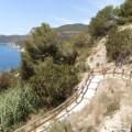 Imagen de la costa de Es-Cubells, en Ibiza. Se ve la rampa por la que se baja al mar, así como zona de monte verde, y algo de mar.